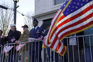 veteran smiling as parade comes by and American flag flies