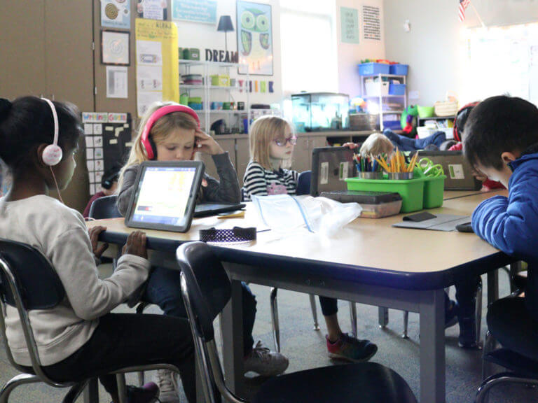 elementary students at a desk block, working on tablets