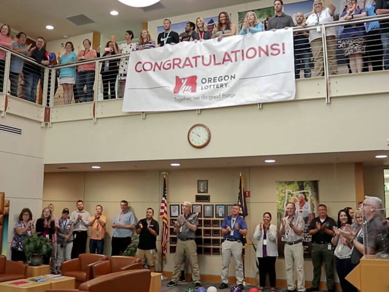 Lottery staff gathered in lobby with Congratulations banner at winner presentation