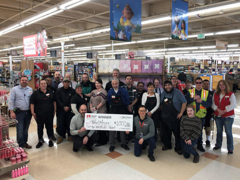 Fred Meyer employees gathered around an oversized check at a Winner Retail bonus event