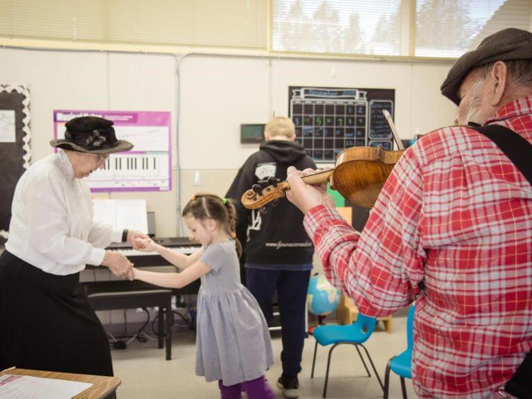 Fiddle player visiting a classroom