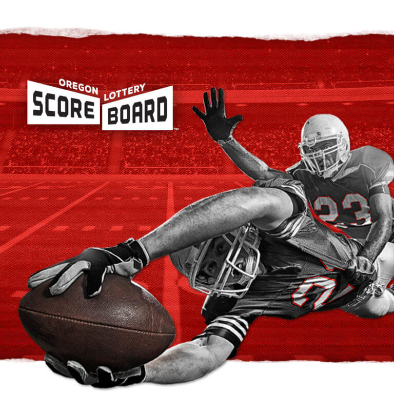 football player diving for football, being tackled, by scoreboard logo