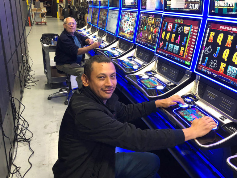 two employees repairing a line of video lottery machines in a warehouse
