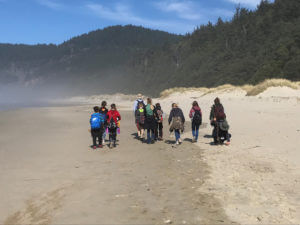 students and teachers walking down a beach