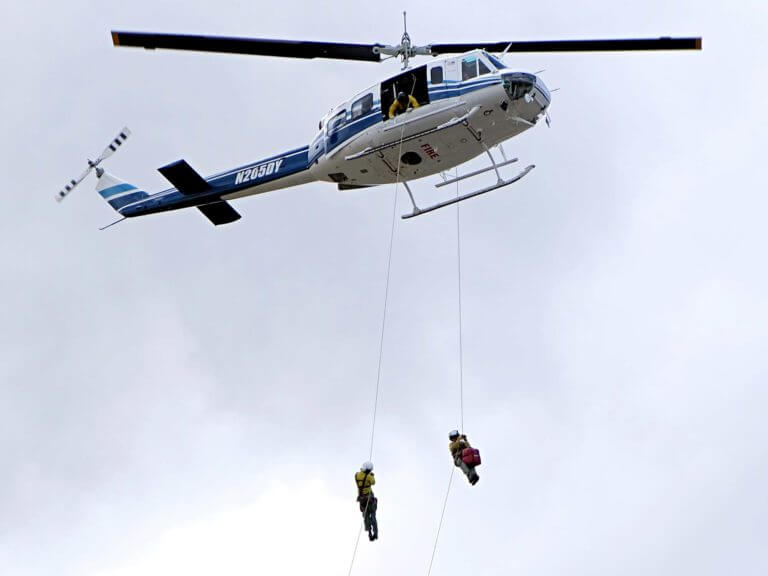 Rappellers descend from helicopter