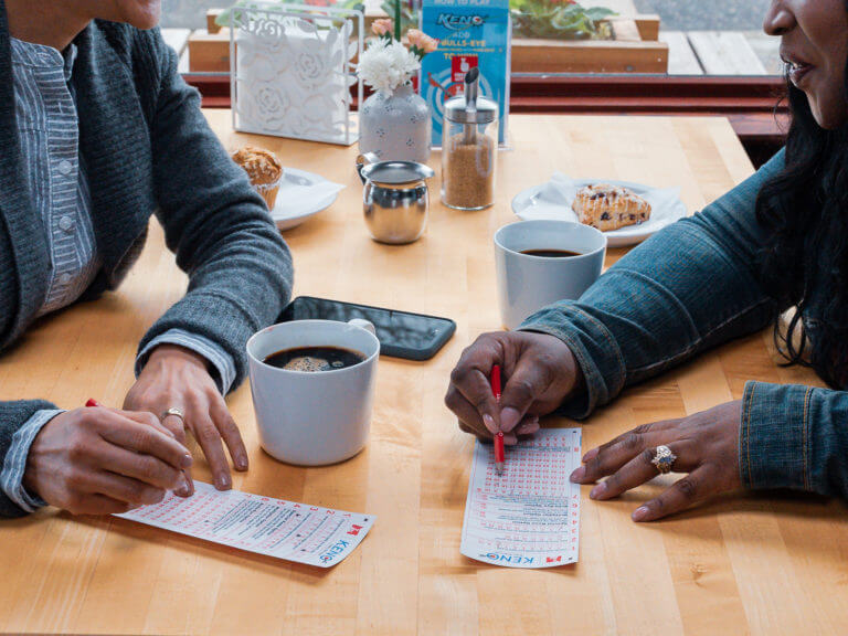 close up of two people filling out a Keno slip while drinking coffee