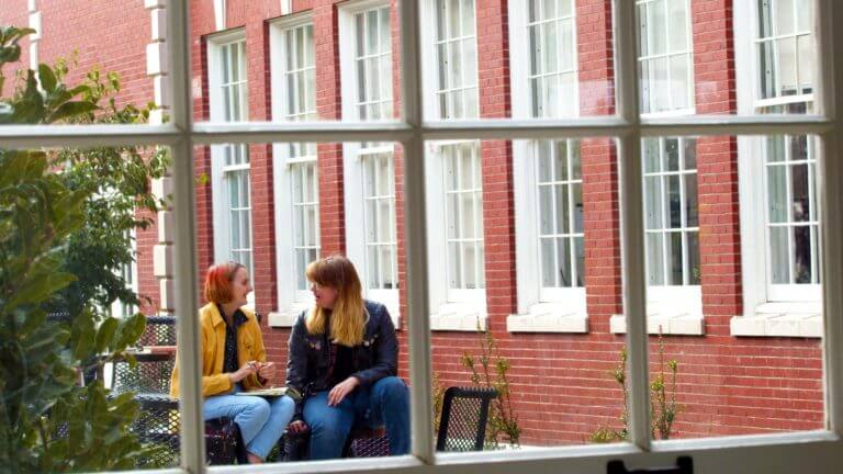 two students talk outside of window