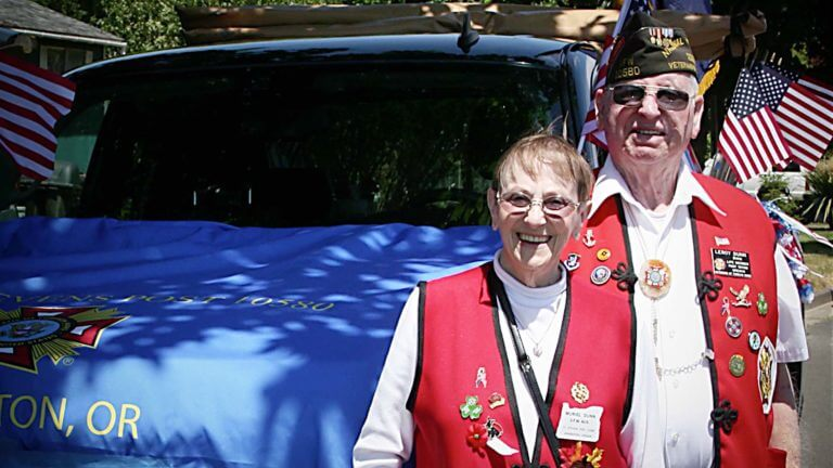 Male and female veterans in red vests with pins