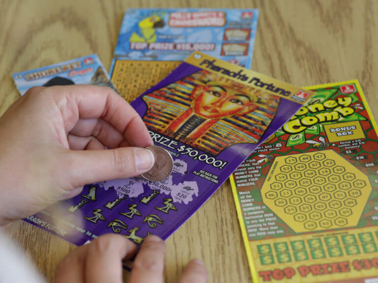 close up of hands scratching a Pharaoh's Fortune Scratch-it ticket